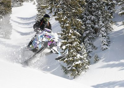 Professional snowmobile rider performing jump trick