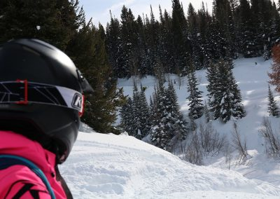 Snowmobile rider looking at mountain trail