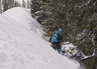 Professional snowmobile rider on mountain trail