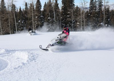 Two people riding snowmobiles on snow covered mountain