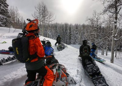 Group of 4 people on snowmobiles on mountain