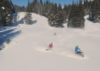 Group of snowmobile riders on snowy mountain