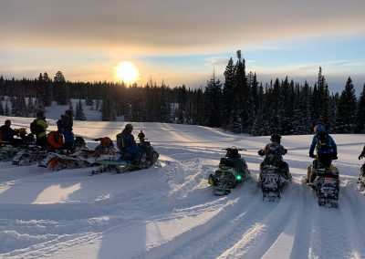 Group of people on snowmobiles watching sunset on mountain