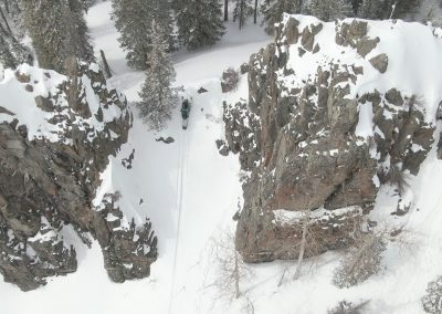 Person riding on snowmobile through cliffs
