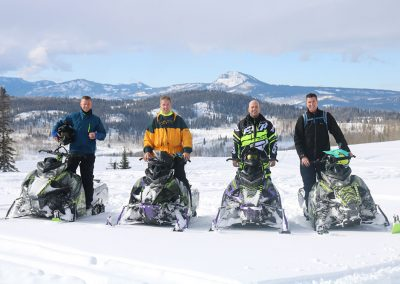 4 men sitting on snowmobiles on a snow covered mountain in Steamboat springs CO