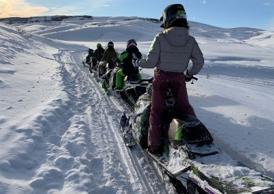 group of snowmobile riders in a line on a snow covered mountain in Steamboat Springs