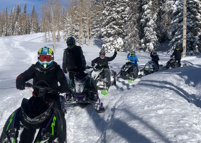 group of snowmobile riders on snowy trail