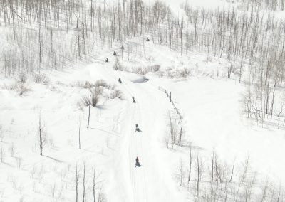 Group of snowmobiles on snowy mountain trail