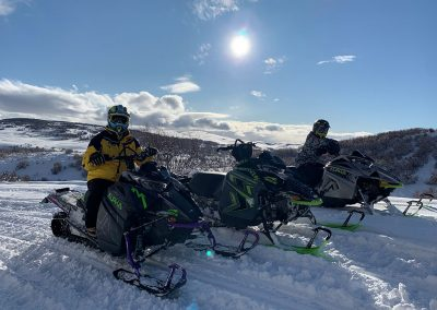 Two people sitting on snowmobiles